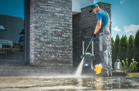 Pressure Washer Cleaning in Front of the House. Caucasian Men in His 30s Washing Concrete Bricks Driveway in Sunny Summer Day. Cleaning Around the House Concept.